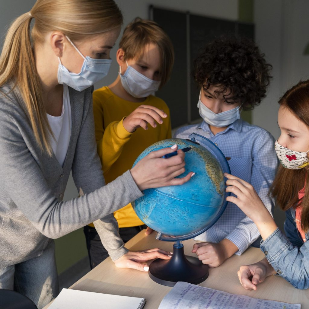 female-teacher-with-medical-mask-teaching-geography-with-earth-globe-in-class