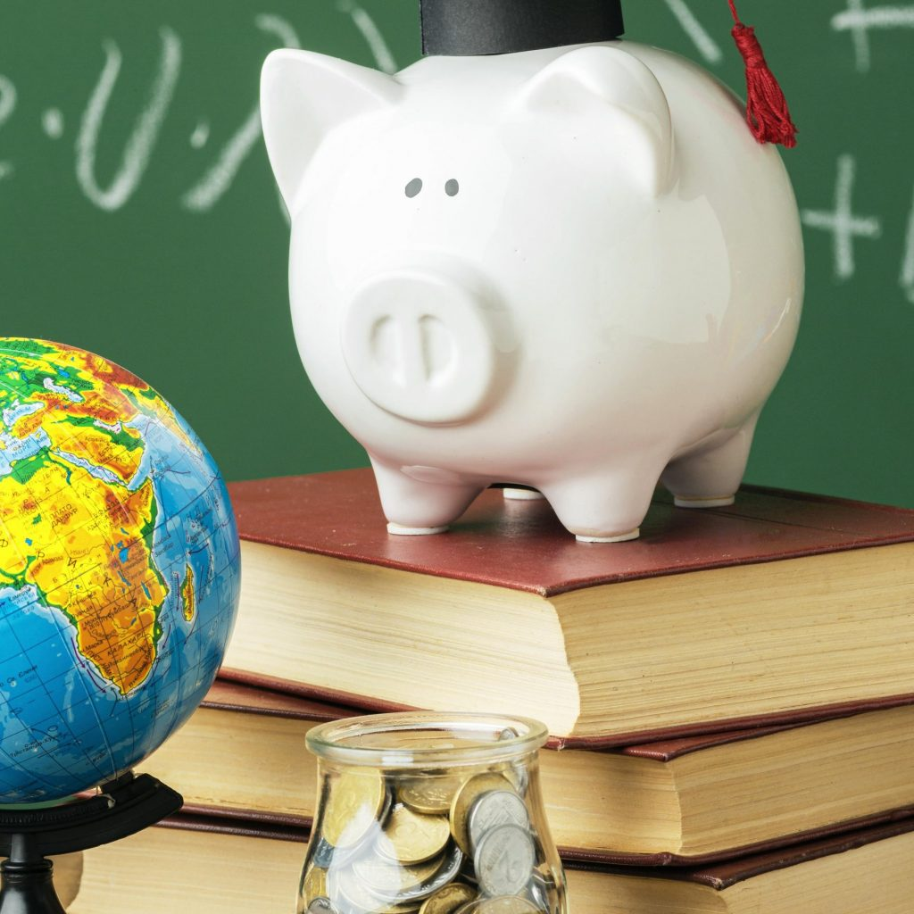 front-view-of-academic-cap-on-piggy-bank-and-stack-of-books